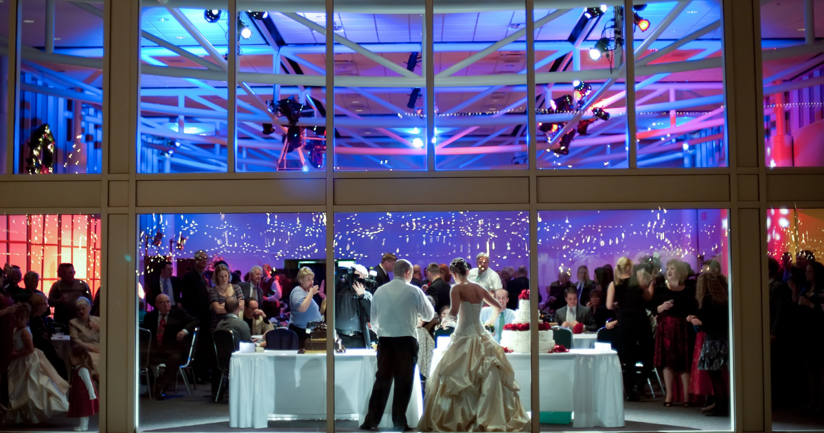 A bride and groom cut a cake inside The Atrium.